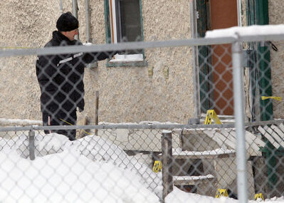 Police forensic officers gather evidence while investigating the death of Zenon Sylvester Bozynski in January 2011.