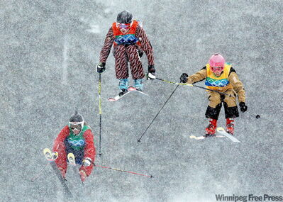 Canadian Ashleigh McIvor (centre) becomes first-ever women's Olympic ski-cross champ.