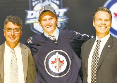 Defenceman Jacob Trouba, the ninth pick, shares the stage with Jets head coach Claude Noel (left) and GM Kevin Cheveldayoff in Pittsburgh Friday night.