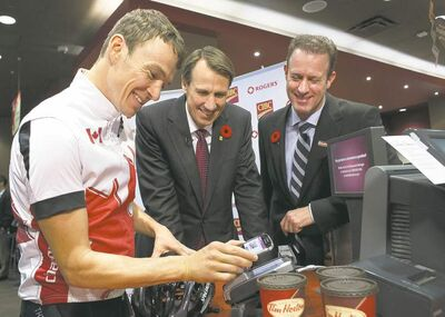 Olympic gold medal-winning triathlete Simon Whitfield (left), with David Robinson of Rogers (centre)  and David Williamson of CIBC, pays with his smartphone at a Tim Hortons in Toronto on Friday.