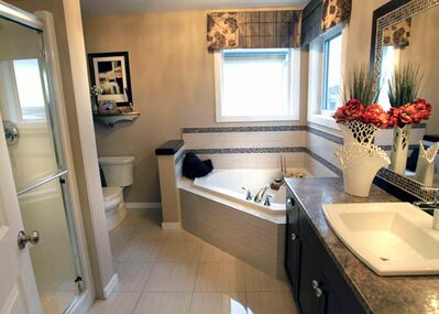 The ensuite is huge and luxurious, with a heated tile floor, corner jetted tub with tile surround and two windows above either side, and a five-foot shower.