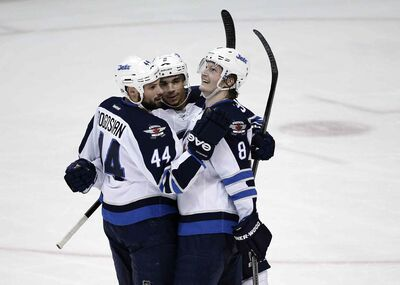 Winnipeg Jets' Evander Kane, center, celebrates his goal with Zach Bogosian, left, and Jacob Trouba during the second period Tuesday in Anaheim, Calif. The Jets beat the Ducks 3-2.