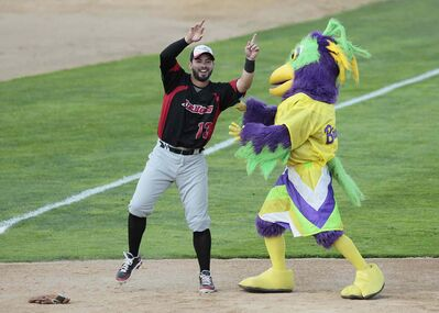 Grand Prairie Air Hogs' Adel Nieves jokes around with a mascot during Tuesday's American Association All-Star game at Shaw Park.