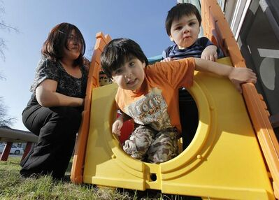 Ashley Vivier plays with her sons, Alex, 4, and Chris, 2. She says education is key to her family's success.