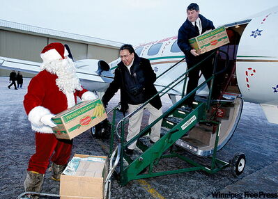 Santa and Grand Chief David Harper hand boxes of goodies to Perimeter Airways pilot Trevor Ryder.