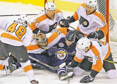 John Woods / The Winnipeg Free Press Winnipeg Jets� Andrew Ladd gets crushed by Philadelphia goalie Ilya Bryzgalov and the rest of the Flyers Tuesday at the MTS Centre.