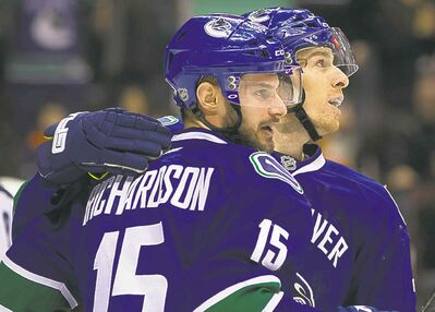 Brad Richardson (left) and David Booth celebrate Richardson's tip-in power-play goal against the Jets during the first period in Vancouver.