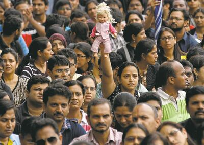 Aijaz Rahi / The Associated PressA mother holds up a doll belonging to her child Saturday at a protest demanding arrests in the rape of a six-year-old girl at a school in Bangalore, India.