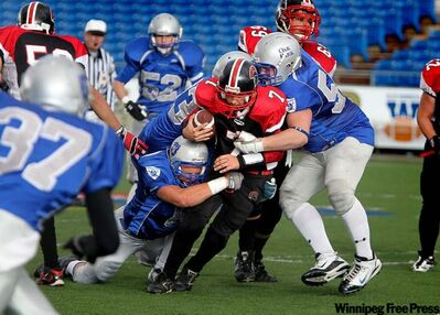 The Sisler Spartans' James Wilson (7) gets tackled by Oak Park Raiders players during the high school football quarter-finals at Canad Inns Stadium Wednesday. Oak Park won 36-15.