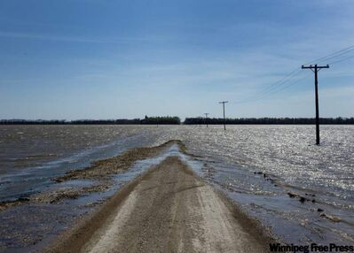 Waters from the Assiniboine River dike  breach flood across a  road Tuesday  near Newton.