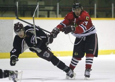 Charleswood Hawks' Doug Lawrence checks Kevin Coulombe of the Pembina Valley Twisters during Game 3 of the MMJHL final series at Eric Coy Arena Sunday.