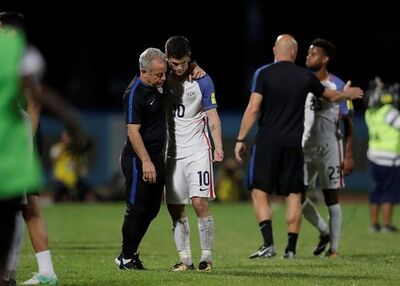 United States' Christian Pulisic, (10) is comforted after losing 2-1 against Trinidad and Tobago during a 2018 World Cup qualifying soccer match in Couva, Trinidad, Tuesday, Oct. 10, 2017. (AP Photo/Rebecca Blackwell)