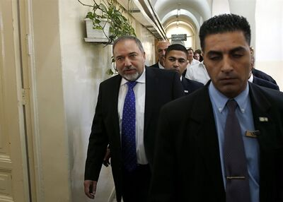 Former Israeli Foreign Minister Avigdor Lieberman, left, enters the courtroom to hear the verdict in his graft trial at the Magistrate Court in Jerusalem Wednesday, Nov. 6, 2013. An Israeli court on Wednesday found Lieberman innocent of all charges, clearing the way for the powerful hard-line politician to return to his post as the nation's top diplomat. (AP Photo/Ronen Zvulun, Pool)
