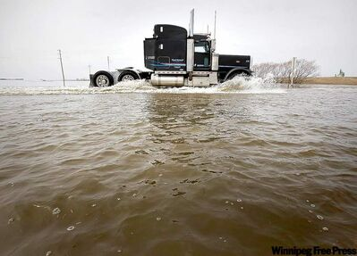 A truck heads north on Tuesday on Highway 75 into the town of Morris, which is surrounded by water from the Morris and Red rivers.