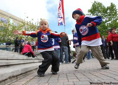 Dylan Bridge, 3, and his brother Aiden, 6, dance around at The Forks on Tuesday to celebrate the return of the NHL to Winnipeg.