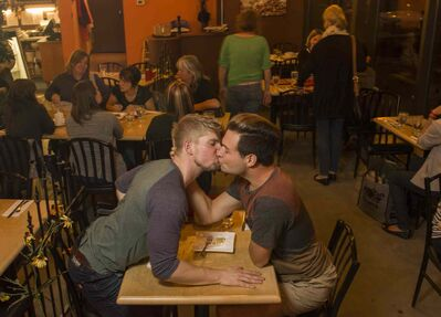 Jonathan Kindzierski (left) and Brett Owen, kiss in a local café.