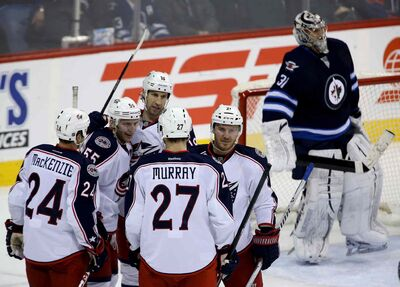 Columbus Blue Jackets' Derek MacKenzie (24), Mark Letestu (55), RJ Umberger (18), Ryan Murray (27) and James Wisniewski (21) celebrate after Letestu's third-period goal on Winnipeg Jets' goaltender Ondrej Pavelec (31) in Winnipeg Saturday.
