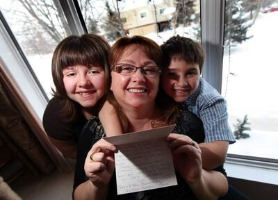 Trina Cimino, with children Kevin, 8, and Sarah, 11, holds a card from the Manitoba School For the Deaf. Kids from the school helped out the family, collecting donations after a holiday break-in.