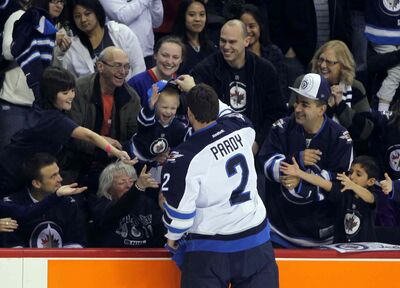 Jets defenceman Adam Pardy gives a hat to a lucky Jets fan during the skills competition at MTS Centre Wednesday night.