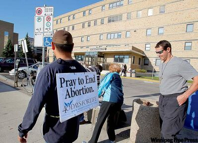Anti-abortion demonstrators hold vigil outside of the Women's Hospital on Notre Dame Avenue Tuesday.