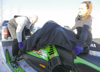 Kevin and Michelle Slezak load up their snowmobiles at The 59er on Highway 59 after hitting the nearby trails.