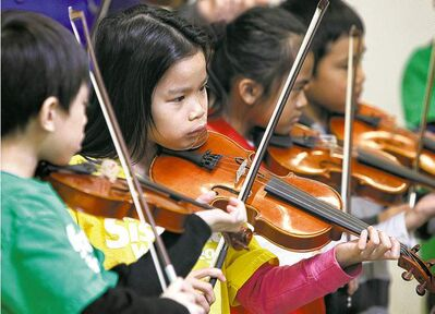 Elwick Community School student, AJ Rosaldo (second from left), 8, plays her violin along with about 30 other students who are part of the Sistema after-school program.