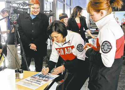 Fan Steven Stevenson gets autographs from Olympians Jill Officer (centre) and Dawn McEwen at the News Cafe.