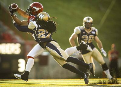 Winnipeg Blue Bombers' Marty Markett, right, covers Calgary Stampeders' Anthony Parker, as he makes a catch during CFL pre-season football action in Calgary on Saturday.