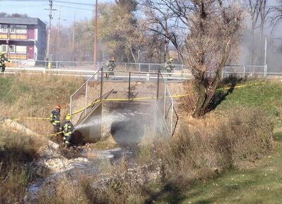 Firefighters battle a blaze at a culvert for the Truro Creek that flows under Portage Avenue near Albany Street in Winnipeg Tuesday afternoon. The fire caused thick smoke that closed Portage Avenue to both eastbound and westbound traffic.  The cause of the fire is unclear.
