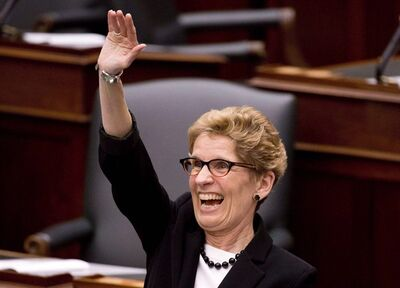 Ontario Premier Kathleen Wynne smiles and waves moments before Ontario Finance Minister Charles Sousa tables the 2013 provincial budget at Queen's Park in Toronto on Thursday, May 2, 2013. Canada's first openly-gay premier, Ontario's Wynne, will march into history later this month when she becomes the first sitting premier to take part in Toronto's annual gay pride parade.THE CANADIAN PRESS/Nathan Denette