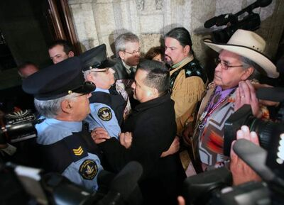 Chiefs and First Nations members try to push their way into the House of Commons as the are restrained by House of Commons guards on Parliament Hill in Ottawa, Tuesday.