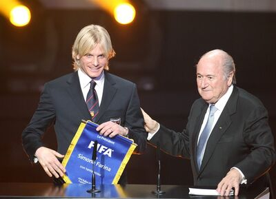FILE - In this Monday, Jan. 9, 2012 file photo Italian soccer player Simone Farina from 2nd League Club AS Gubbio, left, stands next to FIFA President Joseph Blatter at the FIFA Ballon d'Or awarding ceremony in Zurich, Switzerland. Soccer is falling under a cloud of suspicion as never before, sullied by a multibillion-dollar web of match-fixing that is staining increasingly larger parts of the world's most popular sport. In 2011, Italian defender Simone Farina turned down a fixer's offer of $261,500 to throw a game and reported it to police, setting off an investigation that led to scores of arrests. Despite being honored by FIFA, he found himself shunned by those in Italy who considered him a snitch. (AP Photo/Michael Probst, File)