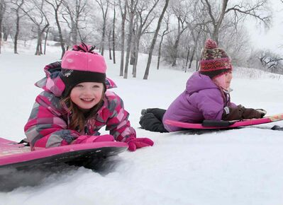 Five-year-old Emily Aikman smiles as she pushes her sled up Omand's Creek hill with her friend  Mya Tottle Saturday morning, while enjoying the warm winter weather with their families.