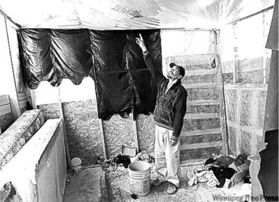 Geordie Rae Jr. checks for leaks in the plastic roofing over his family's temporary housing.