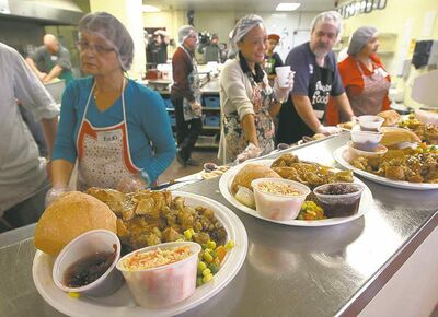 Volunteers serve meals at Siloam Mission on Christmas Eve. More than 300 needy people received traditional meals.