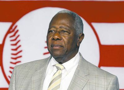 FILE - In this July 28, 2013 file photo, Hall of Famer Hank Aaron walks on stage during the Baseball Hall of Fame induction ceremony in Cooperstown, N.Y. Atlanta police say they've made an arrest in a burglary at Aaron's home. Police Sgt. Greg Lyon said one suspect was in custody Monday night, Aug. 5, 2013. (AP Photo/Mike Groll, File)