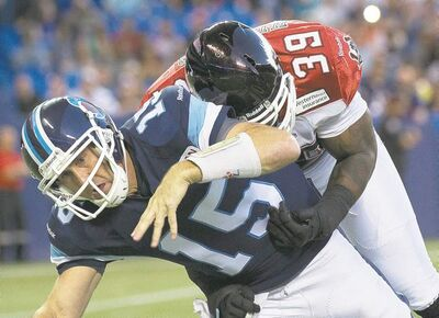 Argos quarterback Ricky Ray (left) suffered a shoulder injury on this hit from Stampeders defender Charleston Hughes.