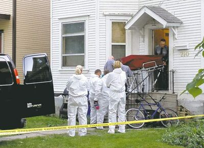 A body is removed from house on Chestnut Street Wednesday.