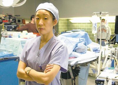 "Actress Sandra Oh poses for a portrait on the set of ABC's new medical drama ""Grey's Anatomy,"" Wednesday, Feb. 23, 2005, in Los Angeles. Oh returns to television after a series of films that included ""The Princess Diaries,"" ""Under the Tuscan Sun"" and the Oscar-winning ""Sideways,"" which was directed and co-written by her husband, Alexander Payne. (AP Photo/Matt Sayles)"