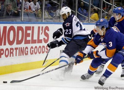 Winnipeg Jets left-winger Kenndal McArdle (23) challenges New York Islanders defenceman Travis Hamonic (3) in the first period of their NHL hockey game at Nassau Coliseum in Uniondale, N.Y.