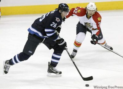 The Winnipeg Jets' Blake Wheeler (26) stickhandles the puck while the Florida Panthers' Kris Versteeg moves in to check him in the first period at the MTS Centre on Saturday.