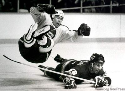 Jets Forward Morris Lukowich is upended by the Calgary Flames' Charlie Bourgeois at the Winnipeg Arena in the early 1980s.