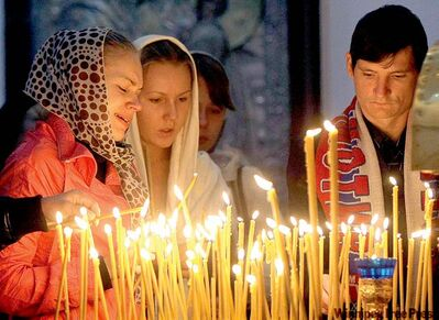 Fans of the Lokomotiv Yaroslavl hockey team light candles and pray during a commemorative service at a church in Yaroslavl, Russia, Thursday.