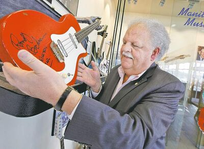 Earl Barish holds Randy Bachman's first electric guitar, one of the items on display in the new Salisbury House restaurant.
