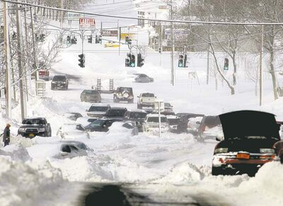 Ed Betz / The Associated PressStranded vehicles litter the roadway along Route 25 in Lake Grove, N.Y., Saturday. Many people abandoned their vehicles along Long Island roadways after they became stuck. First responders rescued a number of people from stranded cars, some having spent the night in frigid temperatures.
