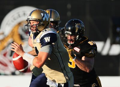 Bombers quarterback Buck Pierce is chased by Hamilton Tiger-Cats' Brian Bulcke during first half. It was one of many times Pierce was on the run — he was sacked six times.