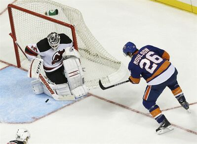 New Jersey Devils goalie Cory Schneider, left, makes a save on a shot by New York Islanders left wing Matt Moulson (26) during the third period of a preseason NHL hockey game, Saturday, Sept. 21, 2013, in New York. The Devils won 3-0. (AP Photo/Julio Cortez)
