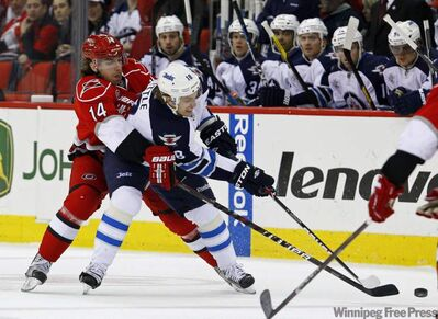 The Carolina Hurricanes' Andreas Nodl and Winnipeg Jets' Bryan Little (18) chase the puck during the first period of their NHL  game in Raleigh, N.C., Monday.