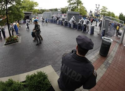A police officer watches an entrance to the Billie Jean King National Tennis Center during the U.S. Open tennis tournament in New York, Wednesday, Sept. 7, 2011. From bomb-sniffing dogs to pat-downs of fans, security will be tight at 13 NFL games and the U.S. Open tennis tournament on Sunday, the 10th anniversary of the 9-11 terrorist attacks.(AP Photo/Charlie Riedel)