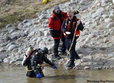 A police diver enters Sturgeon Creek in Woodhaven Park on Wednesday.